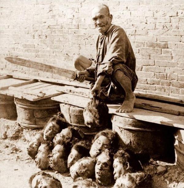 Палач вместе с головами своих жертв - участников Боксерского восстания. Пекин, Китай. 1901 год.