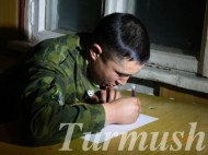 The soldier is writing a letter to his parents that he will send via a postman.